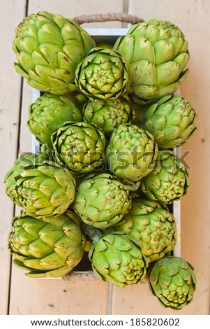 Artichokes in a wooden box. Above view. - stock photo