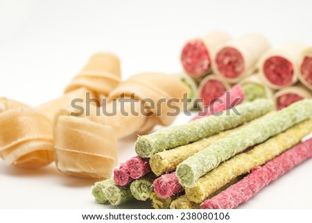 Artificial bones and colorful sticks for dog treat with vitamin and oral health on white background  - stock photo