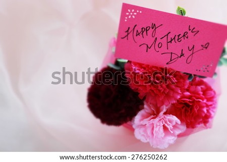 artificial carnation bouquet and hand written message card for Mother's day image - stock photo