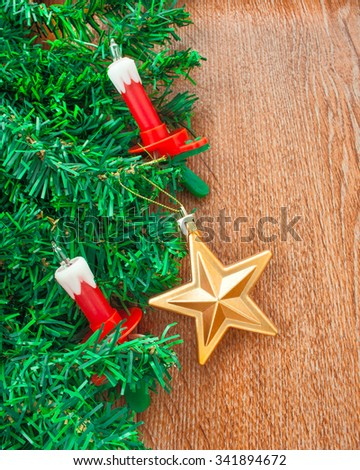 Artificial Christmas tree, electric candles, and gold star on a background texture of oak - stock photo