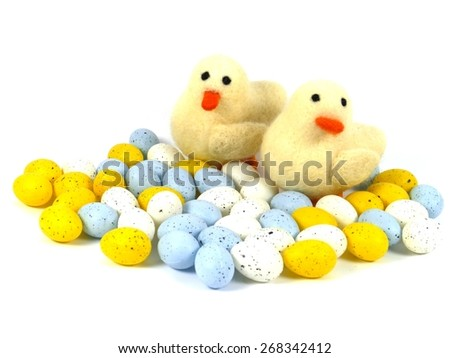 Artificial easter eggs in pastel colors and two ducklings over white - stock photo