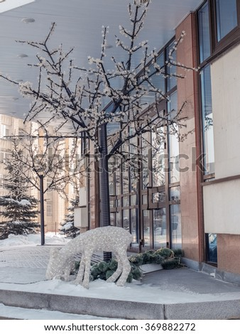 Artificial fawn and a tree in front of the bank in the winter