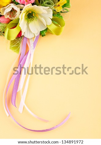 artificial flowers and streamers on cream background with place for label relamy