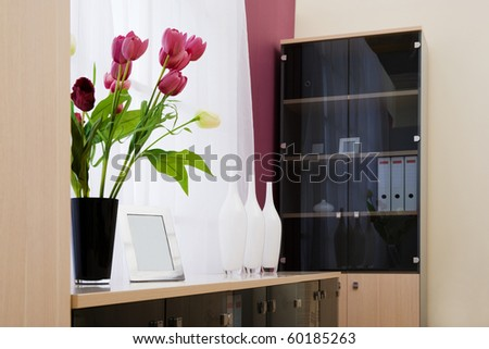 Artificial flowers at a window at office - stock photo