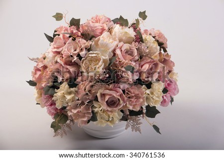 Artificial flowers bouquet in the vase isolated on white - stock photo