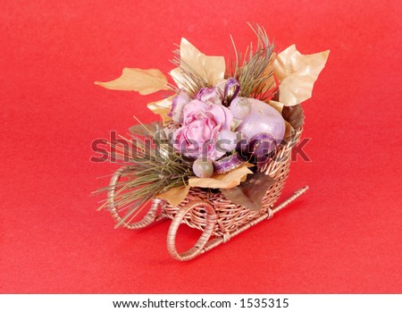 Artificial flowers in a sleigh on red background. - stock photo