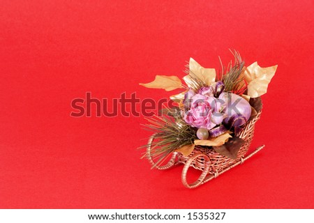 Artificial flowers in a sleigh on red background with space for copy. - stock photo