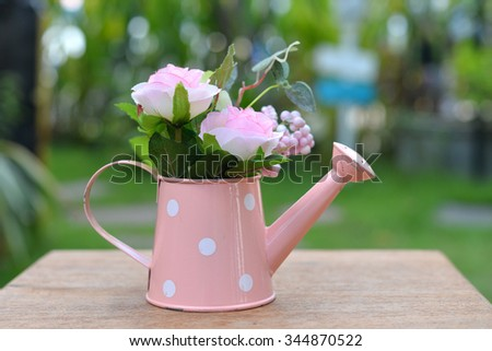 Artificial flowers in pink watering - stock photo