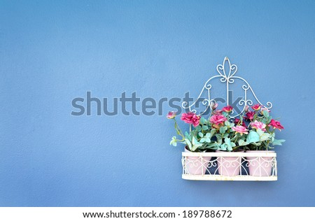 Artificial flowers on blue wall , Vintage style - stock photo