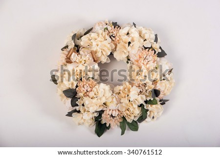 Artificial flowers wreath isolated on white - stock photo
