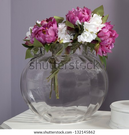 artificial pink and white peony in glass vase standing on table