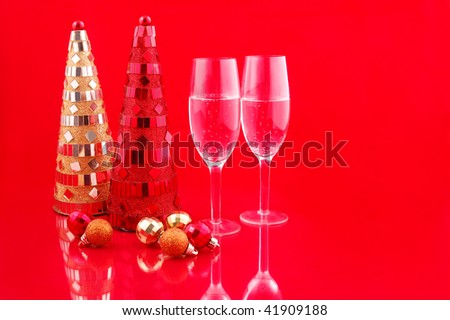 Artificial red and yellow christmas trees and champagne on red background - stock photo