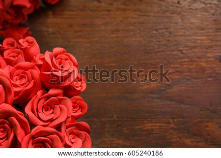 Artificial red rose Flowers on  wood  background.selective focus, copy space
