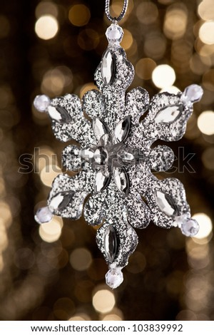 Artificial Snowflake in Silver shining over a golden background - stock photo