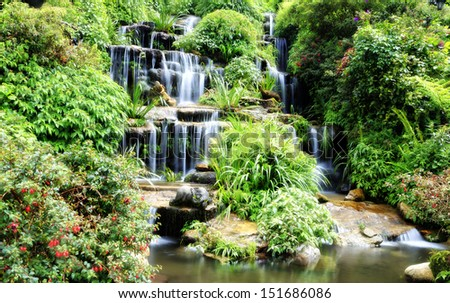 Artificial waterfall in flower garden, Thailand  - stock photo
