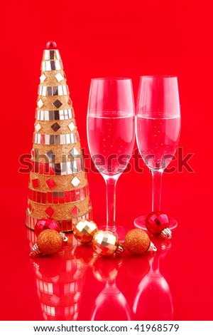 Artificial yellow christmas tree and champagne on red background - stock photo