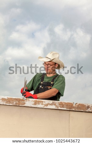 artisan doing carpentry on a wooden construction using a hammer for a big srew