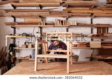 Artisan furniture designer and carpenter in his woodwork studio, with shelves of pieces of wood, while working at his workbench, carefully sanding a chair frame - stock photo