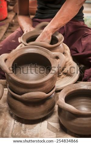 Artisan hands making clay pot - stock photo