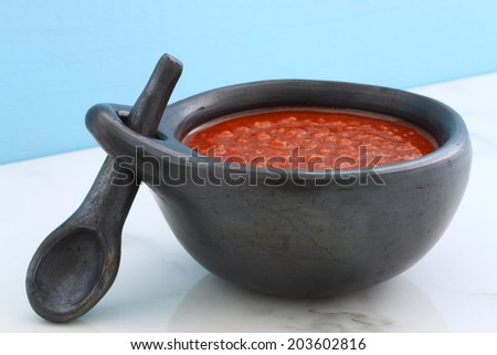 Artisan mexican red hot sauce on retro vintage carrara marble in beautiful terracotta pot, perfect for all your Mexican, tex-mex recipes and sides. - stock photo