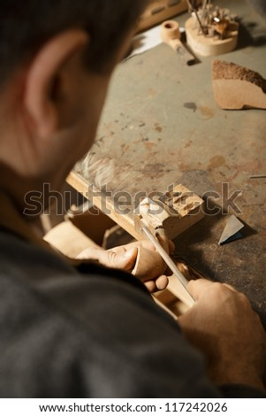 Artisan processing billet with file tool rear view - stock photo