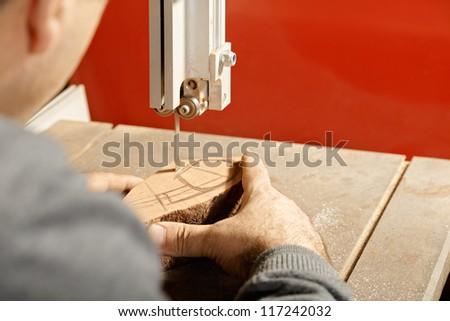 Artisan sawing billet at bandsaw while making smoking pipe rear view - stock photo