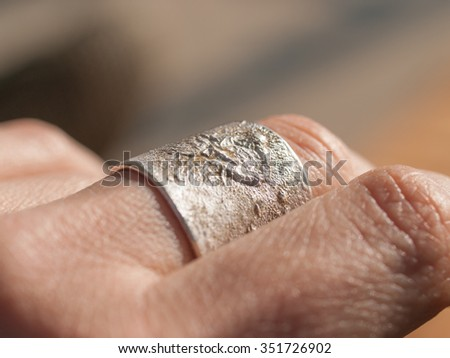 Artisanal silver ring close up on middle finger of woman's hand. Ring made by Aaron Maya.