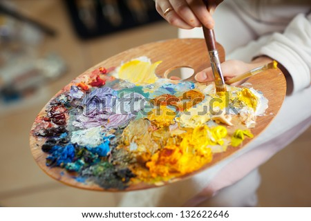 artist brush mix color oil painting on palette is holding in his hand closeup - stock photo