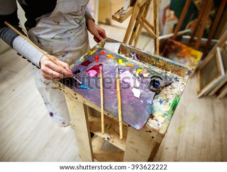 artist draws a picture in an apron, easel and paint palette - stock photo
