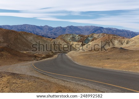 Artist Drive. Curve of winding lane in heart of Death Valley. Asphalted road between sand hills with mountains and blue sky partially obscured by clouds in horizon - stock photo