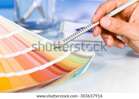 Artist hand pointing to color samples in palette with pencil - stock photo