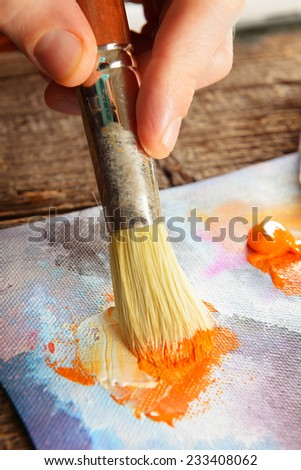 Artist hand with brush in acrylics paints on canvas - stock photo