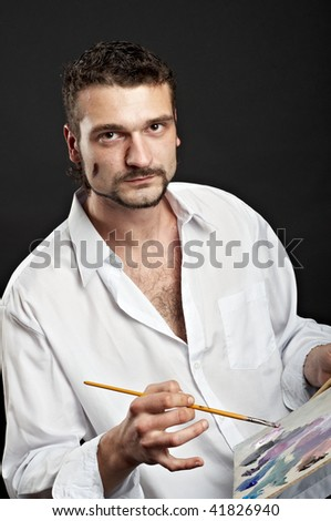 artist in a white shirt with a brush and palette - stock photo