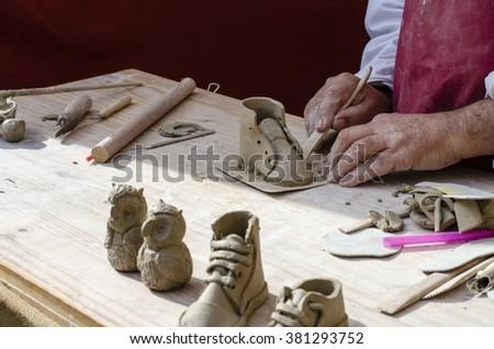 Artist man hands working clay to create handicraft art - stock photo