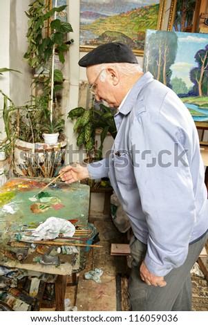 Artist mixing paints on palette sideview - stock photo