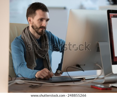 Artist or designer drawing something on graphic tablet at the office - stock photo