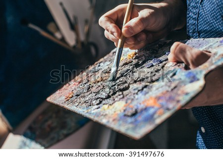 Artist painting an abstract oil picture - stock photo