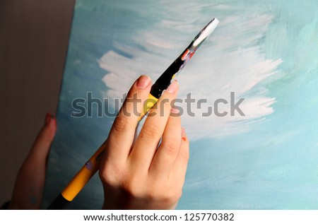 Artist�¢??s hand holding a paintbrush - stock photo