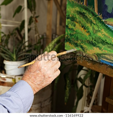 Artist's hand with paintbrush at painting process - stock photo