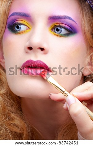 artist's hand with paintbrush painting beautiful girl's lips make up