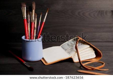 Artist's sketchbook, paintbrush, pencil on the black wooden table close up. horizontal photo. - stock photo