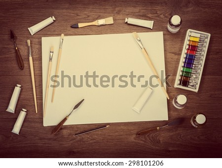Artist's workshop. Canvas, paint, brushes, palette knife lying on the table. - stock photo