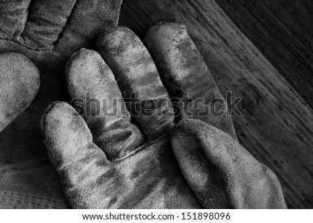 Artistic black and white image of well worn leather work gloves on wood background.  Low key still life with directional, natural lighting for effect. - stock photo
