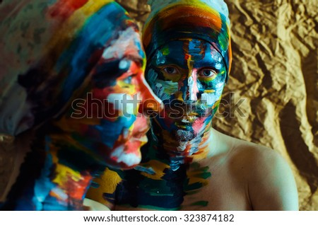 Artistic colorful portrait of model man and woman with big blue eyes and creatively painted face - stock photo