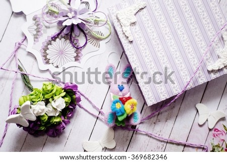 Artistic handmade rabbit, gift box and decorations on wooden table background - stock photo