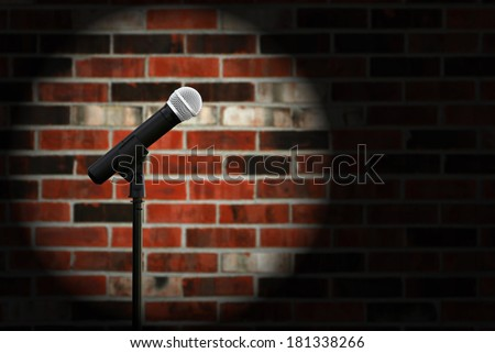 Artistic image of microphone against a rustic brick wall with spotlight effect and copy space.  Closeup with shallow dof. - stock photo