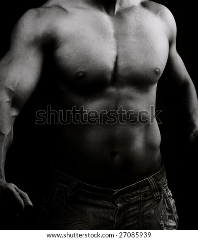 Artistic image of muscular male body in the dark - stock photo