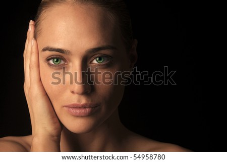 Artistic low key head shot of a woman with vivid green eyes - stock photo