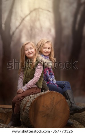 artistic moody outdoor portrait of two blond girls sitting on a log of tree in a woods - stock photo