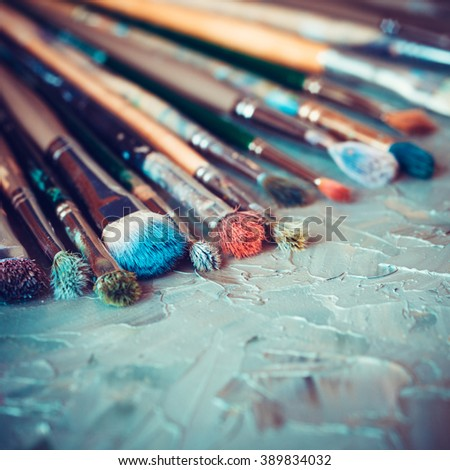 Artistic paintbrushes on artist canvas covered with oil paints - stock photo